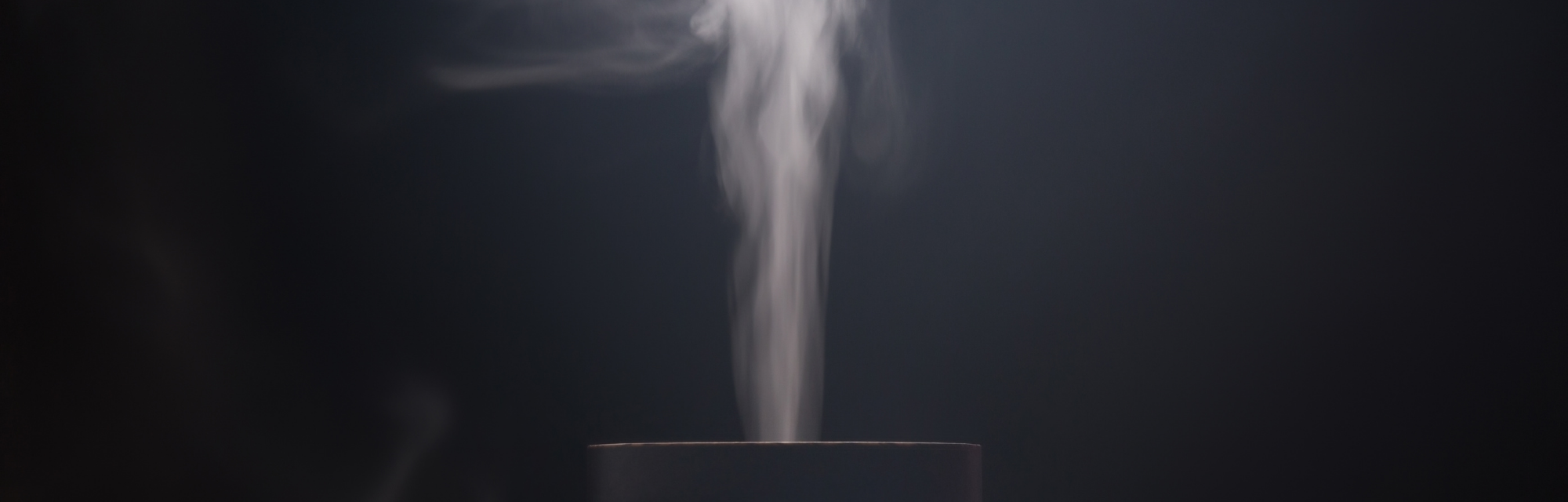 Vapor from an essential oil diffuser wafts into a dark, open room