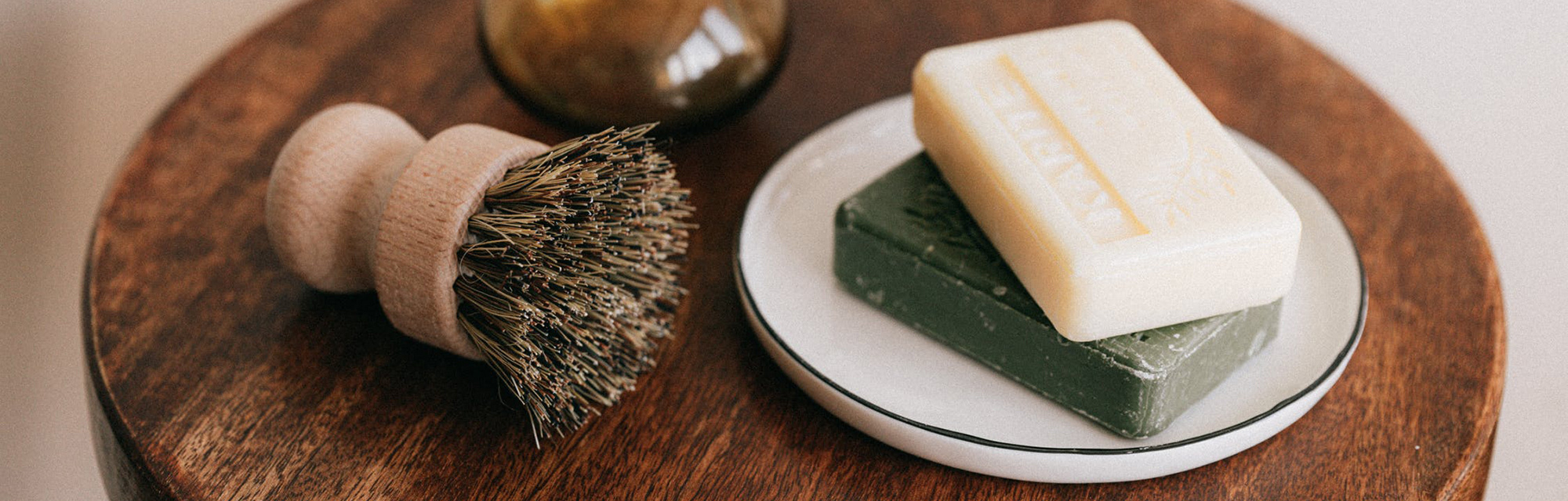 A zero waste compostable dish brush sits on a wooden table next to bars of soap and a vase of dried eucalyptus