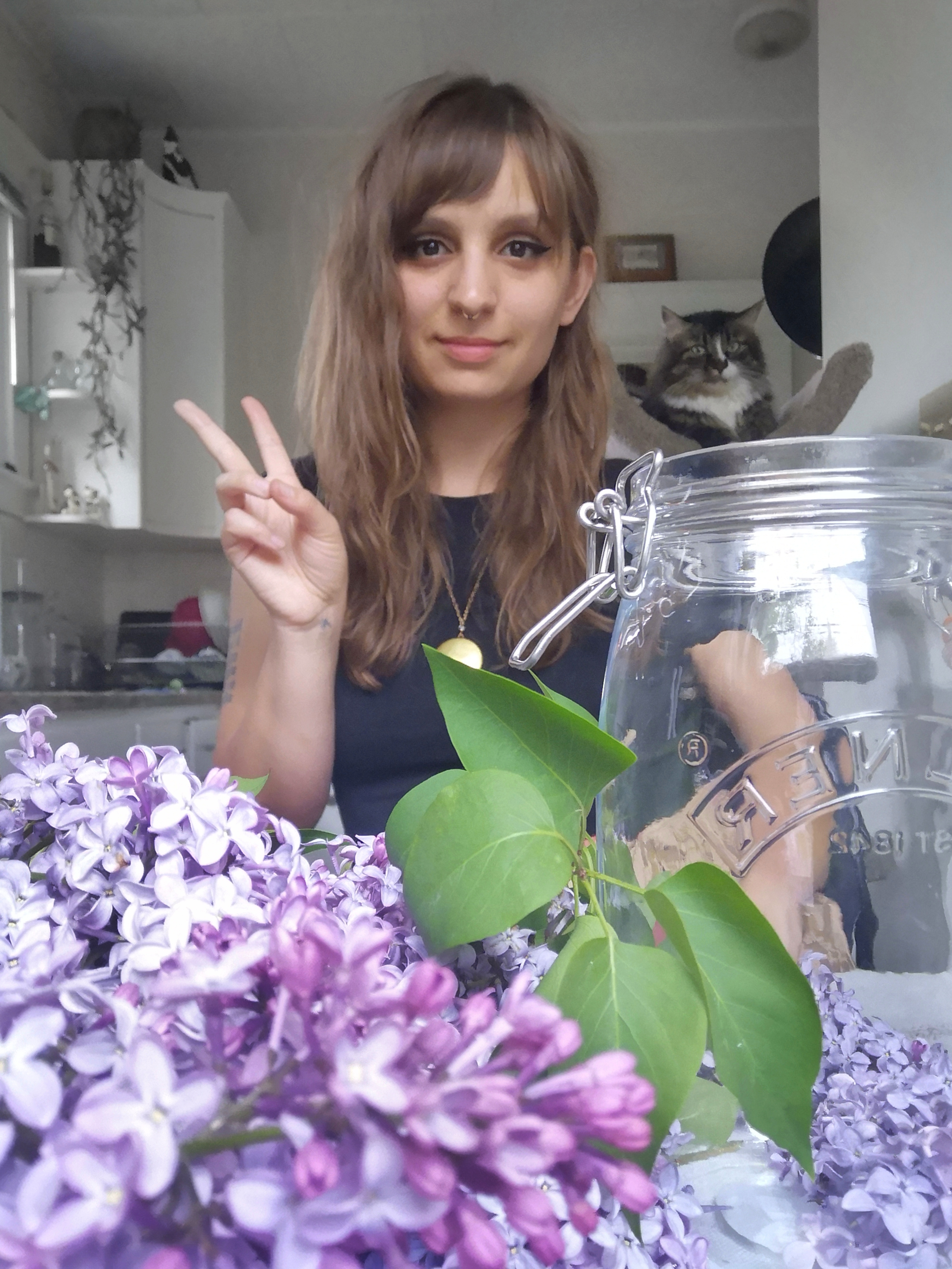 A person is posed behind a bunch of lilacs and a jar.